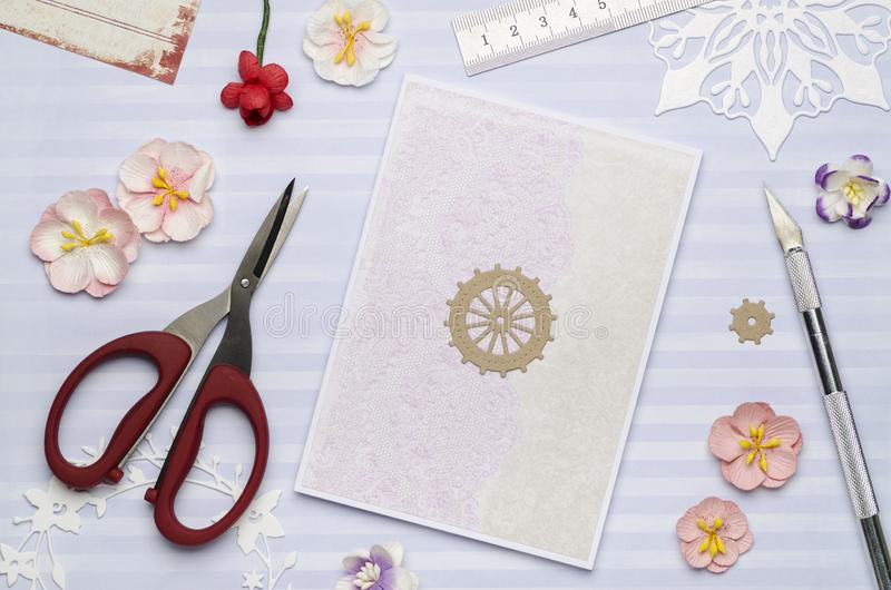 Simple homemade postcard on blue background with scissors, colored paper and paper flowers. Top view, scrapbooking stock photo