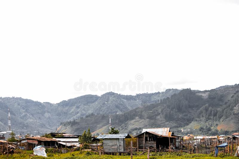 Simple huts of coffee farmers. Simple hut tower valley farmers peacefull land montain sky horizon grass stone village field trees bush jungle horizon takengon stock photo