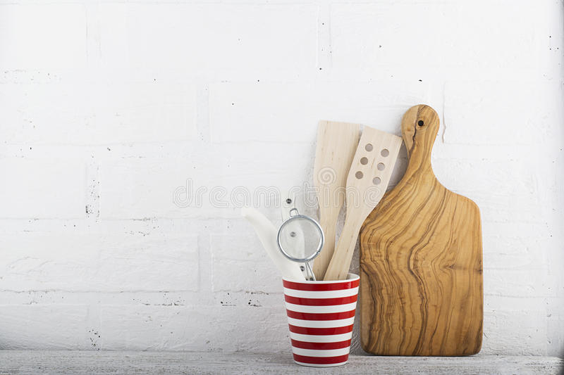 A simple kitchen still life against a white brick wall: cutting board, cooking equipment, ceramics. Horizontal.  royalty free stock photo