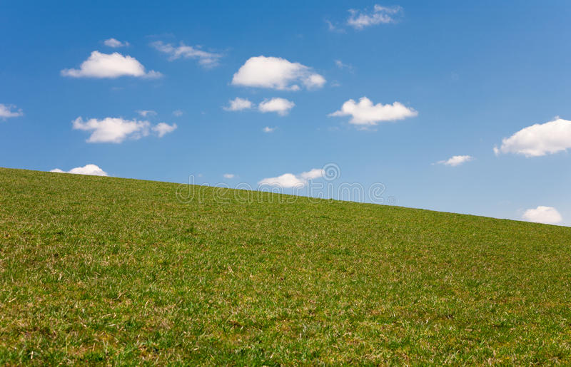 Simple landscape with a grass field and a cloudy sky. stock photo