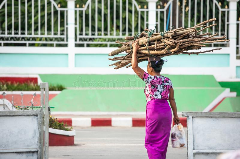 Simple life style at Tarchileik market, Eastern Myanmar. Women burmese in traditional clothing carrying a bundle of firewood on stock photography