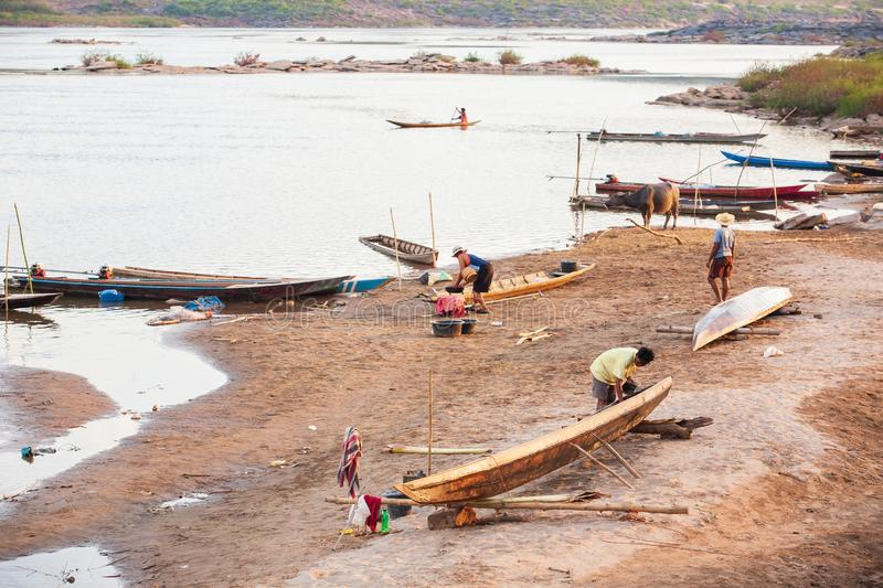 Simple life, tribe Bru village on riverside, ship repair team repairing fishing wooden boat in local shipyard, buffalo, and. Fisherman in the Mekong River. The royalty free stock photo