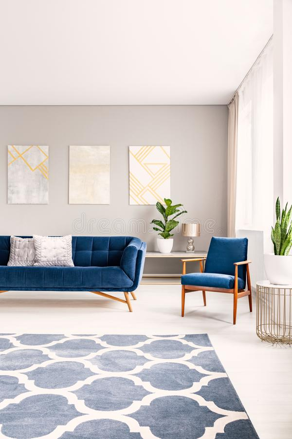 Simple living room interior with a big floor space with a rug. Couch and armchair in the background. Real photo. stock images