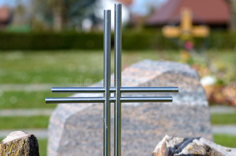 Simple metal cross on a grave in a cemetery stock image