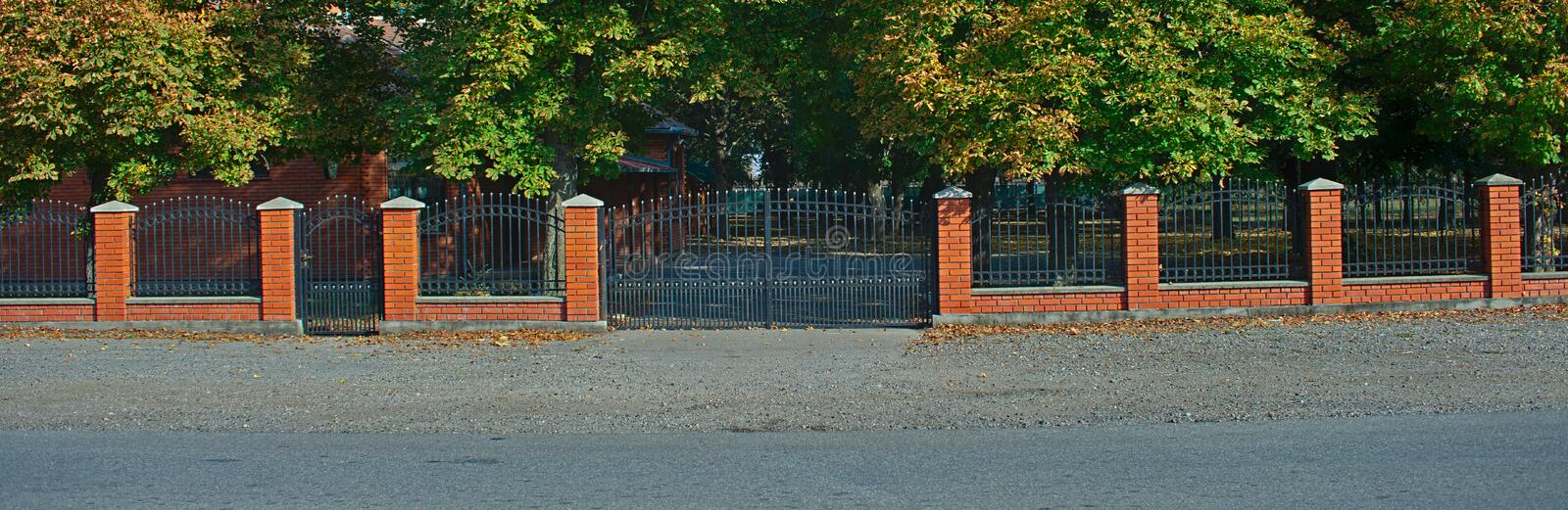 Simple metal fence with red bricks wall and pillars.  royalty free stock photo