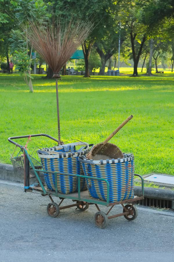 A simple metal gardening trolly, with rubbish bins, broom and dustpan of natural fibers,. A simple gardening trolly, with rubbish bins, broom and dustpan of stock photography