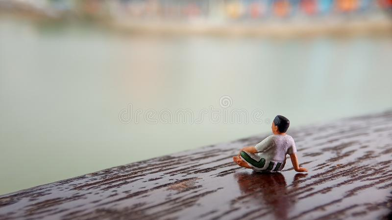 Simple, Mini figure toy old man sit at scratch wooden balcony at river side with copy or negative space for text placement area stock image