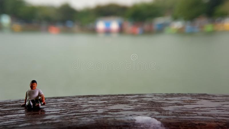 Simple, Mini figure toy old man sit at scratch wooden balcony at river side with copy or negative space for text placement area royalty free stock photos