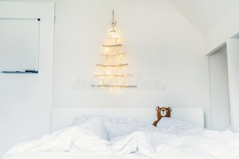 Simple, minimal conscientious Christmass interior design. Unusual Christmas tree made of wooden sticks with a garland on the white stock photography