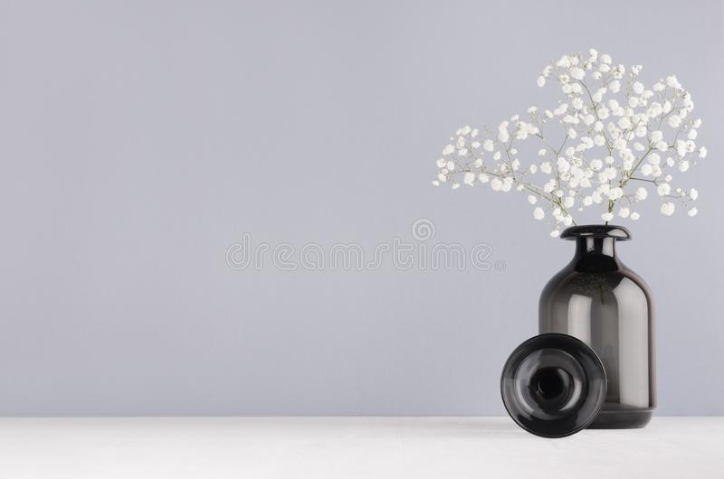 Simple minimalist spring interior in monochrome grey color - black glass circle and vase and bouquet of small white flowers. Simple minimalist spring interior stock image