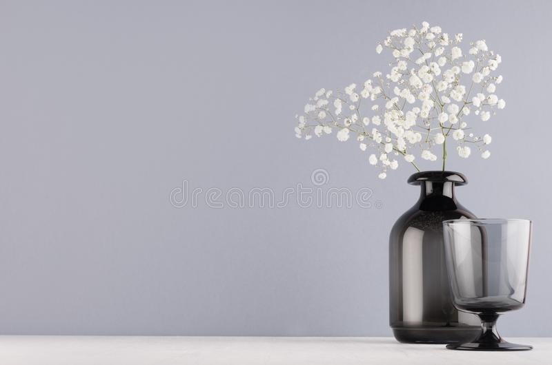 Simple minimalist spring interior in monochrome grey color - black glass drink and vase and bouquet of small flowers on white. Simple minimalist spring interior royalty free stock image