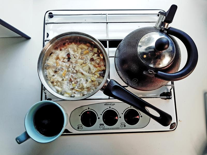 Simple and minimalistic breakfast vintage style with muesli, tea kettle and a mug of coffee on a gas stove kitchenette. Simple and minimalistic breakfast vintage stock photo
