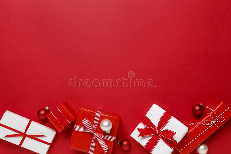 Simple, modern red & white Christmas gifts presents on red background. Festive holiday border. royalty free stock photo