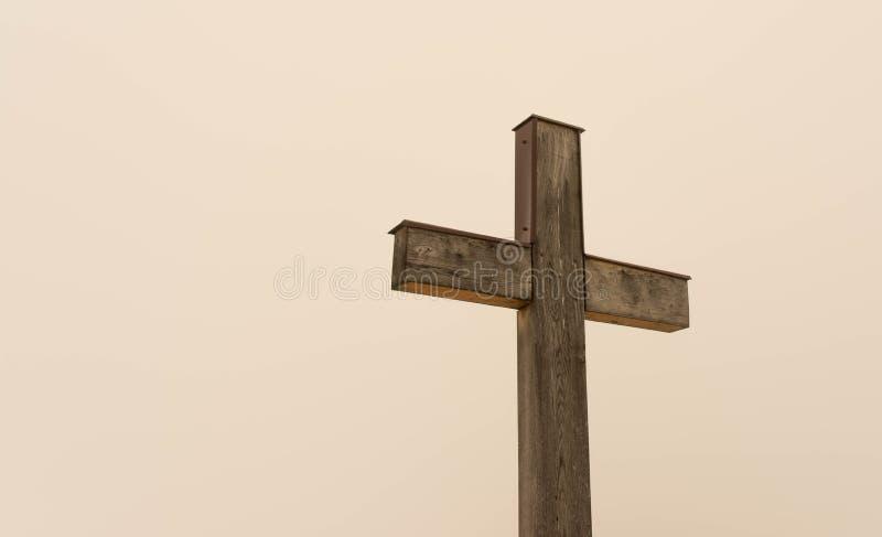 Simple oak wooden cross on natural light. Dense fog on the slightly orange background from the sun stock photography