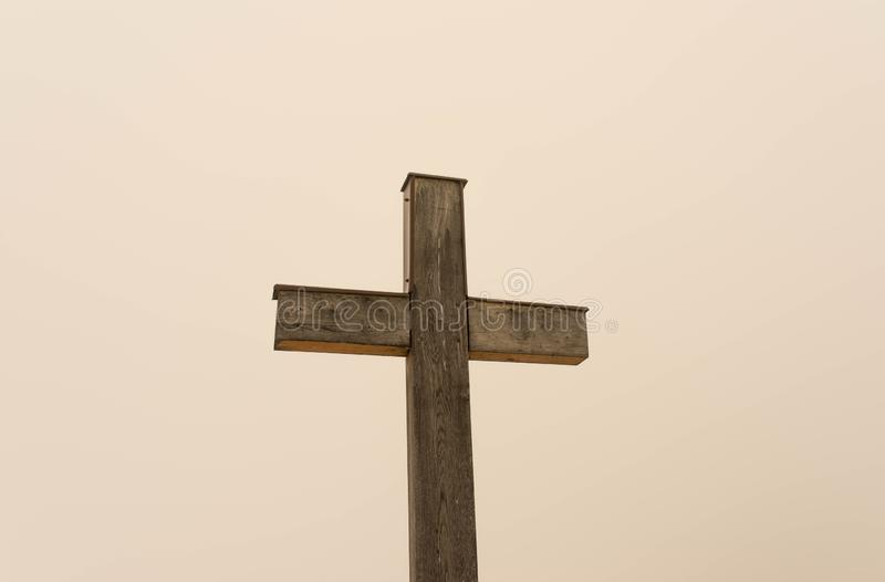 Simple oak wooden cross on natural light. Dense fog on the slightly orange background from the sun royalty free stock photo