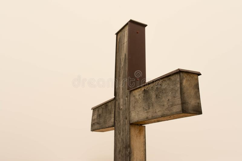 Simple oak wooden cross on natural light. Dense fog on the slightly orange background from the sun stock photos