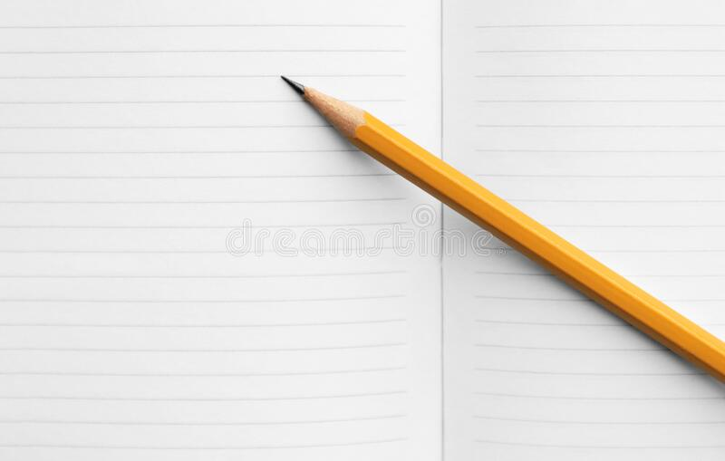 Simple orange pencil on a spread of blank pages of a school notebook, concept back to school, composition book on background for. Educational new academic year stock image