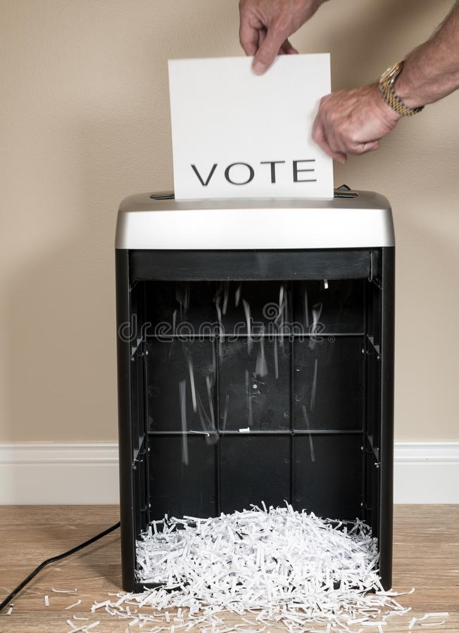 Paper vote being shredded in an office shredder. Simple paper vote being shredded as a wasted vote in an office shredder stock images