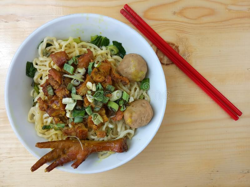 Simple Photo, Flat Lay, delicious Mie Ayam, Chicken Noodle at white bowl and red plastic chopstick at wooden table from indonesia stock photography