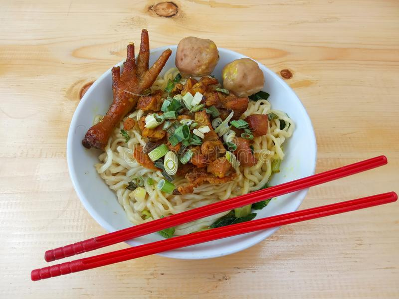 Simple Photo, Flat Lay, delicious Mie Ayam ceker, Chicken Noodle at white bowl and red plastic chopstick at wooden table from indo stock photography