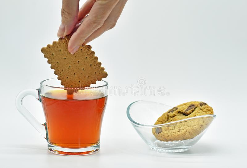 Simple pleasures dipping biscuit in tea stock photos
