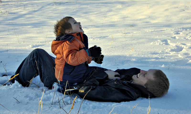 Simple Pleasures. Son on father's stomach in snow, both laughing stock photos