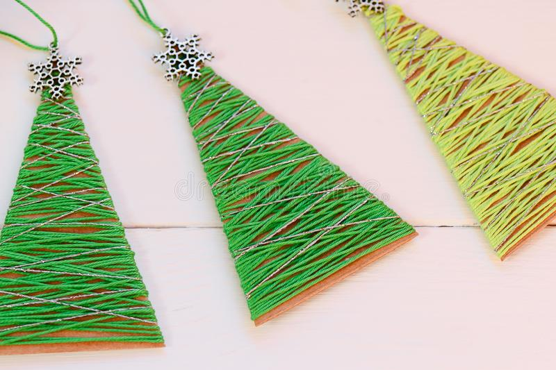 Christmas trees on a wooden table. Creative Christmas trees made of old cardboard box and cotton yarn. Recycled crafts. Simple recycled Christmas decorations royalty free stock image