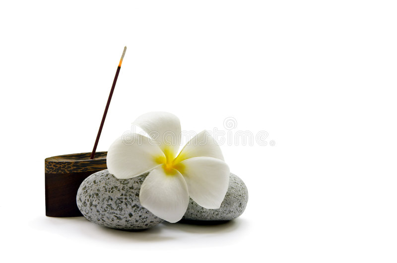 Simple Relaxation. A stick of fragrant Japanese incense, some smooth pebbles and a frangipani flower