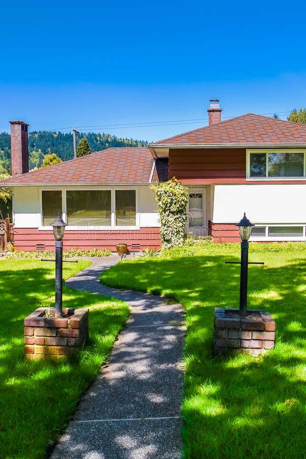 Simple residential house in North America with concrete pathway to the entrance. Family house with tree shadow over the yard. Simple residential house in North royalty free stock image