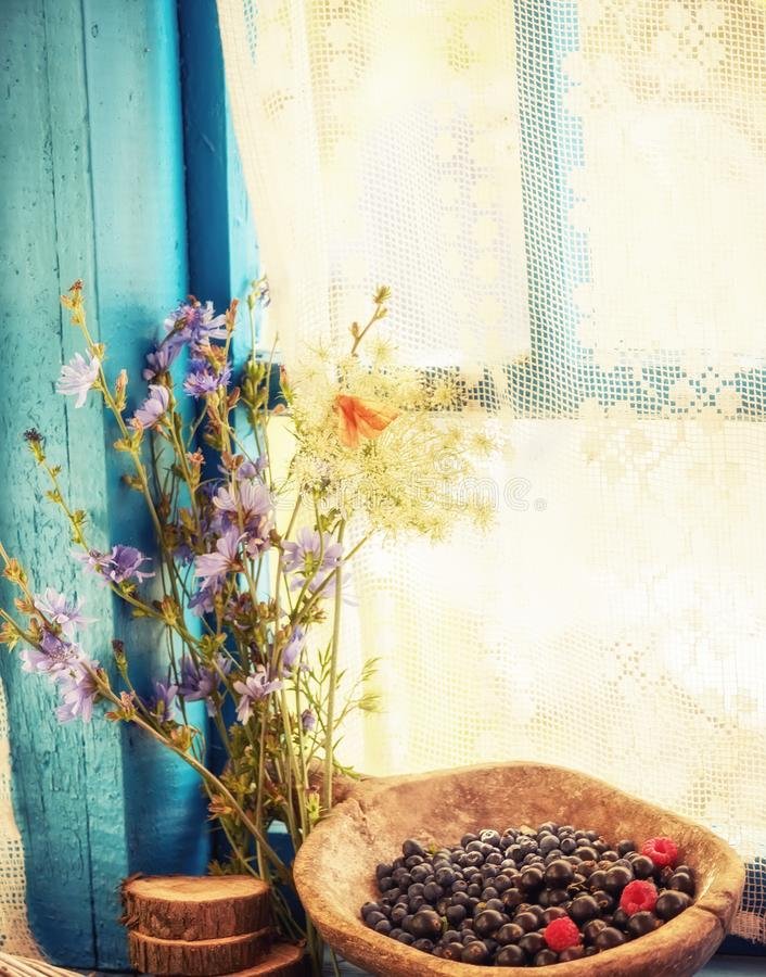 Simple rural still life. Wild berries in a wooden old dish and wild flowers. stock image