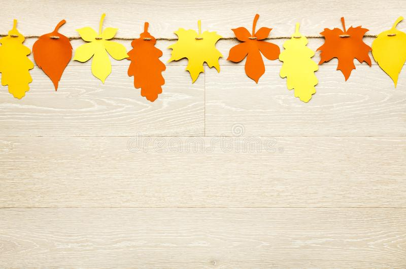 Simple, rustic country style Fall Thanksgiving decorations garland banner of colorful cut paper leaves on whitewashed wood. Background royalty free stock photo