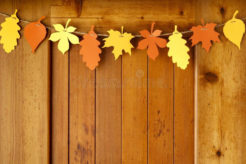 Simple, rustic country style Fall Thanksgiving home decorations paper. Crafts garland banner colorful fall leaves on wood background stock photo