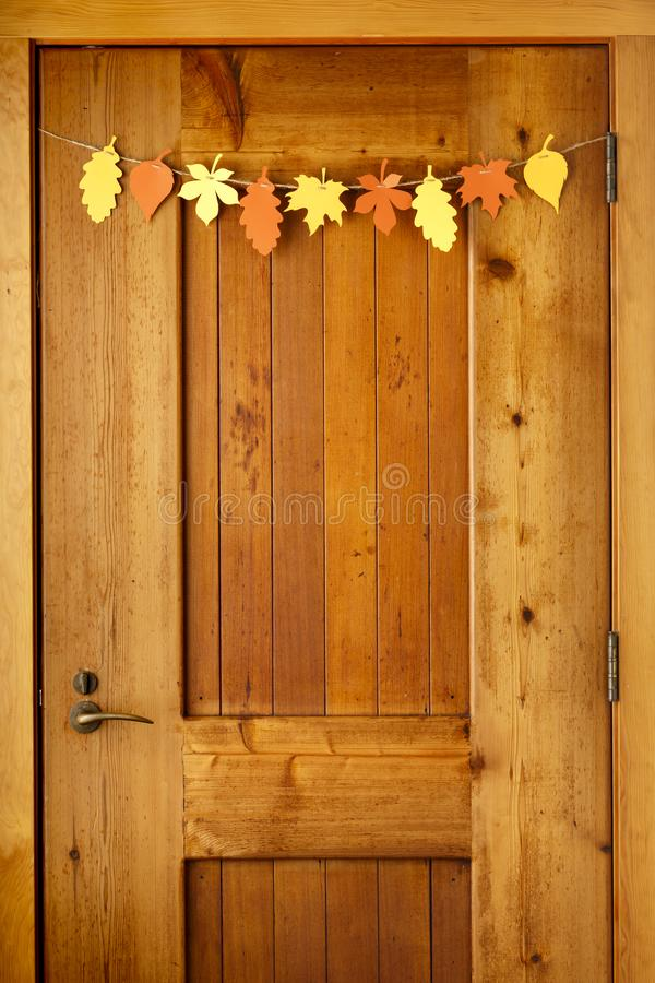 Simple, rustic country style Thanksgiving home decorations paper. Crafts garland banner colorful fall leaves on wooden front door background royalty free stock photography