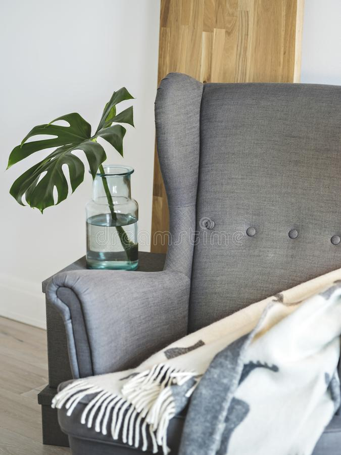 Big armchair for cozy evenings. Simple Scandinavian design with grey armchair for cozy evenings stock images