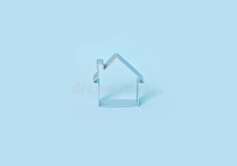 Simple shape of small house isolated on blue background. stock images