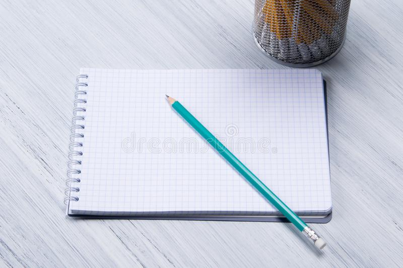 Simple sharp pencil lies on a blank writing pad stock images