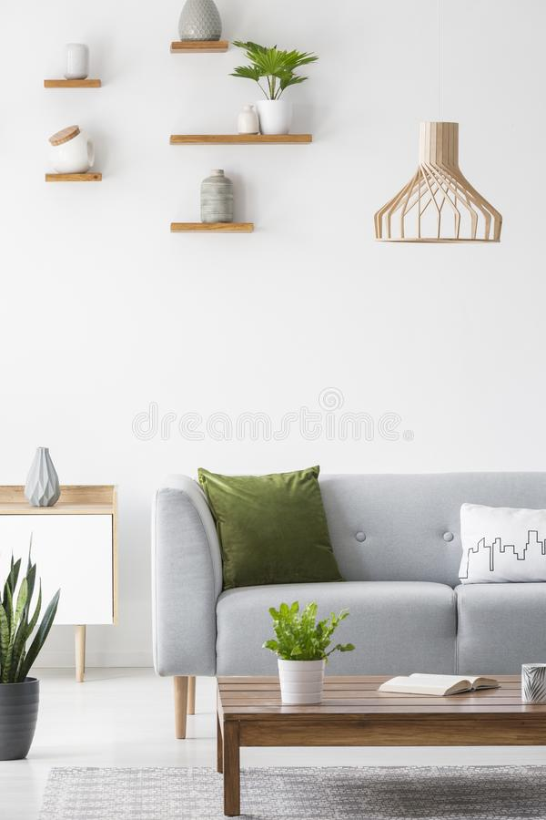 Simple shelves with vases on a white wall and wooden, scandinavian furniture in a bright living room interior with gray decor stock images