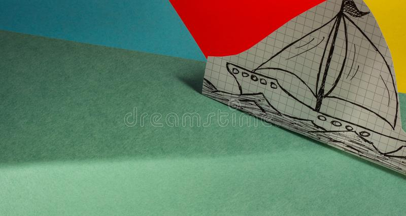 A simple ship drawn on paper stands on a multi-colored cardboard stock photo