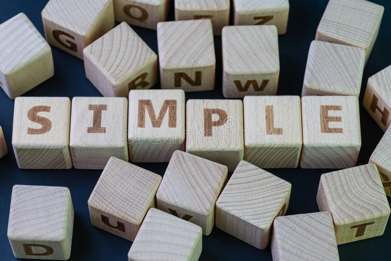 Simple, simplicité, clarté et facilité de gestion concept, cube bloc de bois avec alphabet combinent le mot Simple on black photographie stock