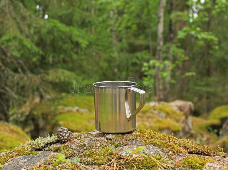 Simple steel mug for camping and a small cone on a stone covered with green moss in a wild forest stock photography