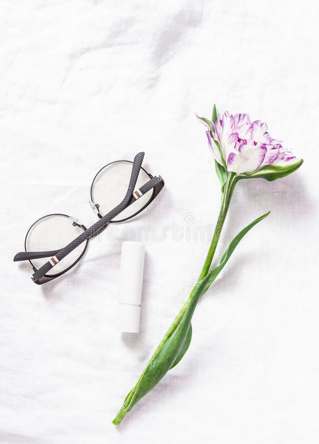 Simple still life on a white background - tulip flower, women`s glasses, lipstick. Free space for text, top view. stock photography