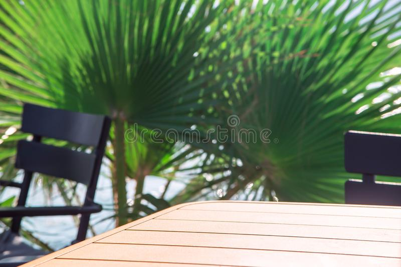 A simple table next to chairs and green palm branches. Copy space royalty free stock images