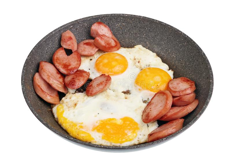Simple village dinner - fried sausage and eggs - in a frying pan with a ceramic coating isolated stock photo