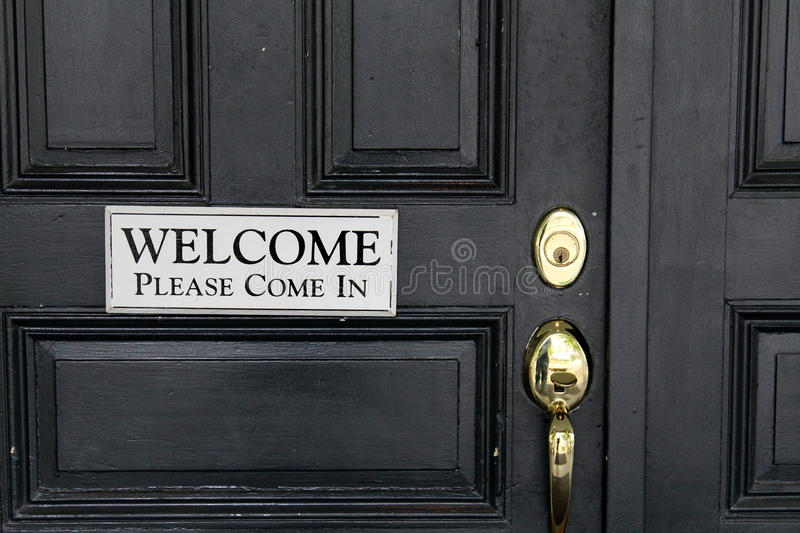 Simple welcome sign on black door. Simple sign with black lettering on white background inviting guests to open black door and come in royalty free stock images