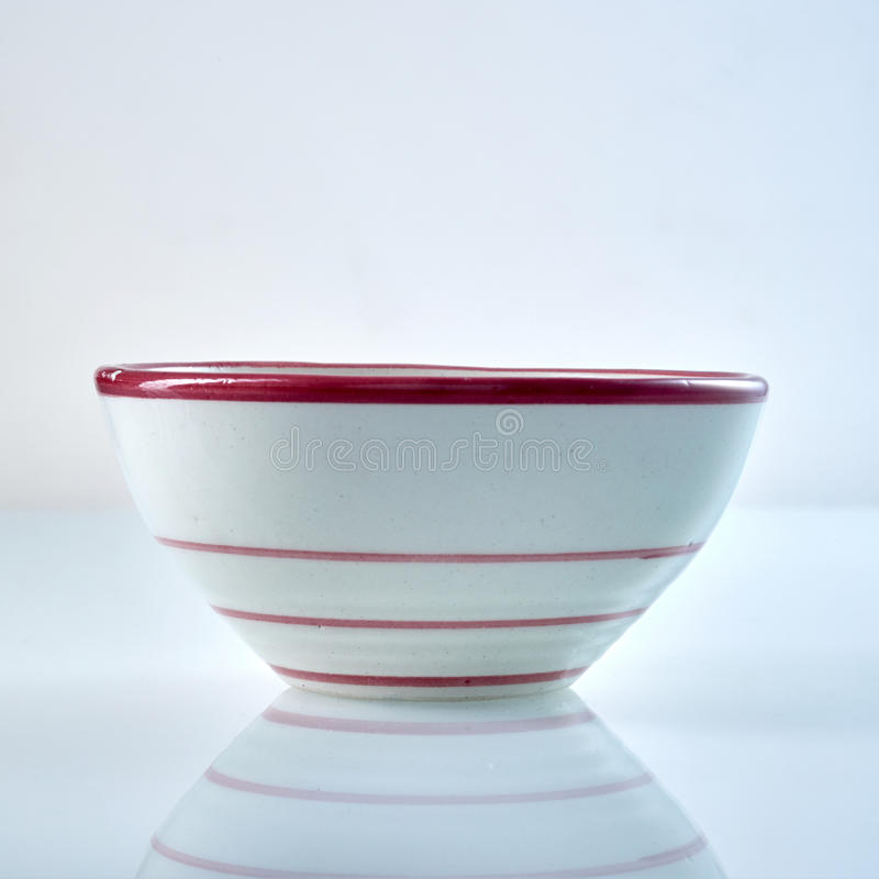 Simple white ceramic bowl with red stripes stock photo