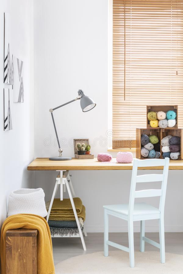 A simple, white chair and a gray desk lamp on a wooden surface in a white tailor workshop interior with colorful yarn and blankets royalty free stock photos