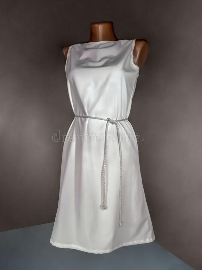Simple white dress with a belt on a mannequin, isolated on a dark background. Mockup or background for overlaying a pattern on. Women`s clothing royalty free stock image