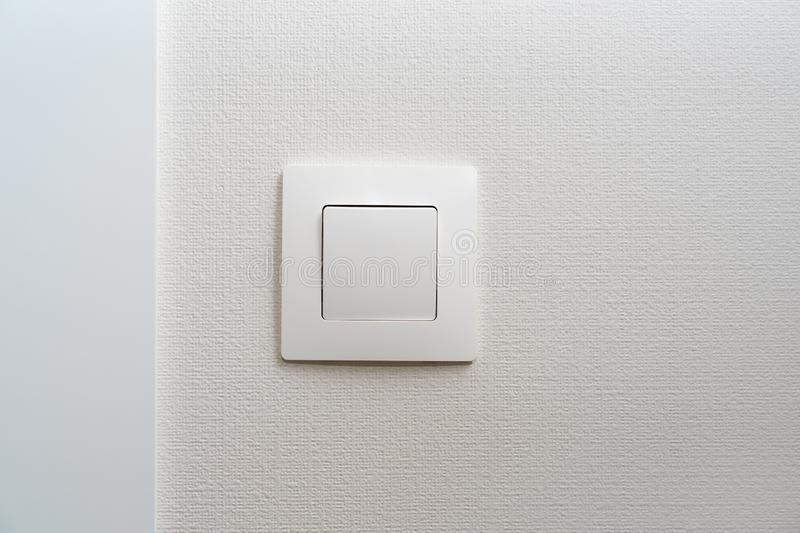 Simple white light switch, turn on or turn off the lights hanging on the white wall in the room.  royalty free stock image