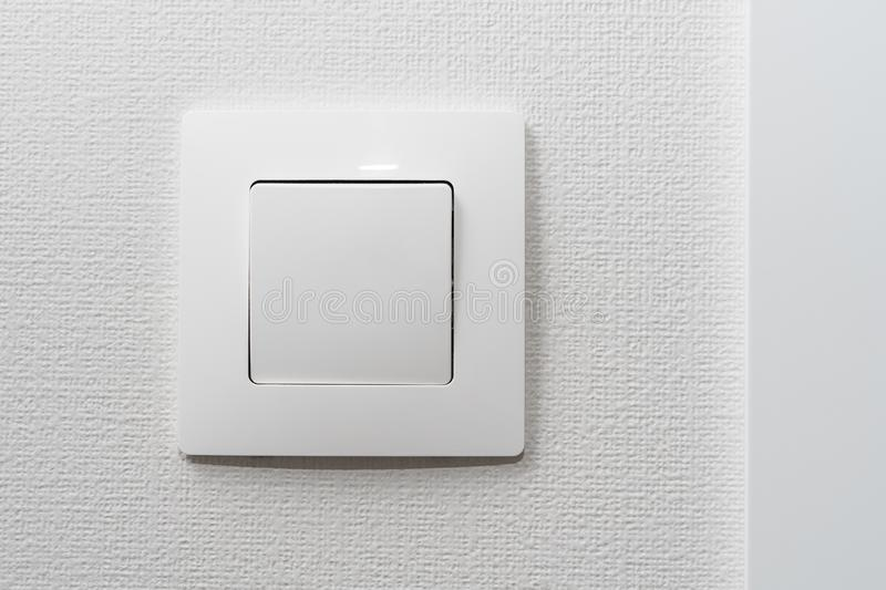 Simple white light switch, turn on or turn off the lights hanging on the white wall in the room.  royalty free stock photo
