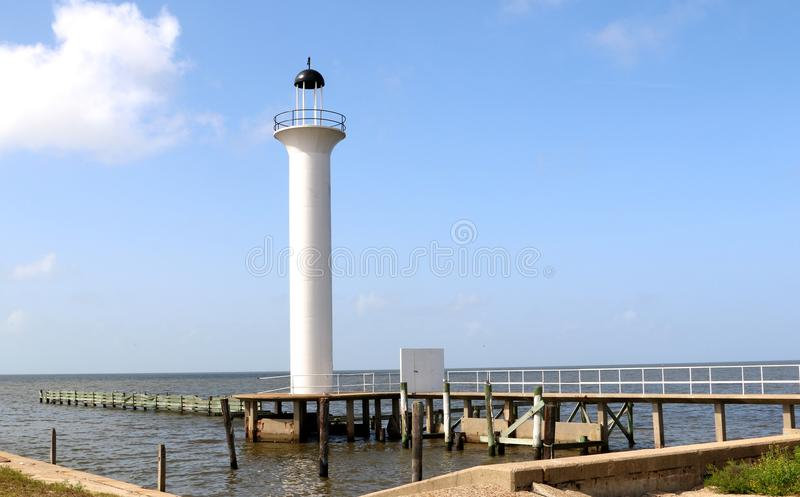 Lighthouse off Mississippi Gulf Coast. Simple white lighthouse situated at the edge of a pier in the Gulf of Mexico harbor at Gulfport Mississippi stock photo